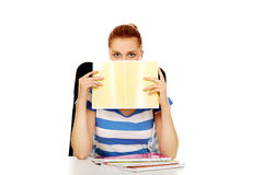 Teenage woman hiding her face behind a notebook Royalty Free Stock Images