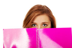 Teenage woman hiding her face behind a notebook Stock Images