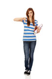 Teenage woman holding a books and shows thumb down Stock Images
