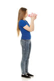 Teenage woman kissing piggybank. Stock Images