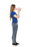 Teenage woman kissing piggybank. Stock Images