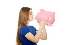 Teenage woman kissing piggybank. Stock Photography