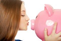 Teenage woman kissing piggybank. Royalty Free Stock Image