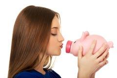Teenage woman kissing piggybank. Stock Photo