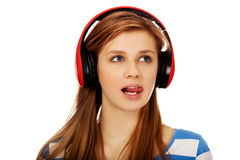 Teenage woman listens to music and shows tounge Royalty Free Stock Images