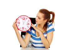 Teenage woman looking at clock Royalty Free Stock Images