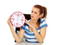 Teenage woman looking at clock Stock Photography