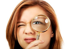 Teenage woman looking through a magnifier Royalty Free Stock Image