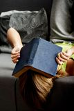 Teenage woman reading a book. Tired teenage woman with a book on her head Stock Photo