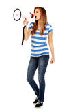 Teenage woman screaming through megaphone Stock Photos