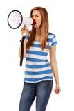 Teenage woman screaming through megaphone Stock Images