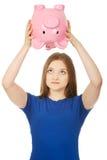Teenage woman shaking piggybank. Stock Photo