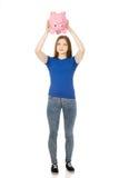Teenage woman shaking piggybank. Royalty Free Stock Images
