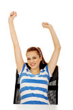 Teenage woman sitting behind the desk with arms up Royalty Free Stock Photography