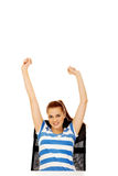 Teenage woman sitting behind the desk with arms up Stock Images