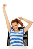 Teenage woman sitting behind the desk with arms up Royalty Free Stock Photos