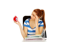 Teenage woman sitting behind the desk and holding alarm clock Stock Photos