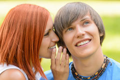 Teenage woman whispering to her boyfriend outdoors Stock Photography