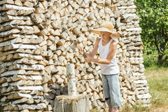 Teenage woodcutter splits woods. Teenage woodcutter splits dry woods at local farm Stock Photo