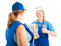 Teenage Worker Has Great Attitude. Teenage worker gives the thumbs up sign as her boss hands her the mop.  Isolated on white Royalty Free Stock Image