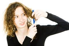 Teenaged blondes M?dchen mit dem Haar Haarbehandlungsproblem verwirrend - K?mmen des gelockten Haares lizenzfreie stockbilder