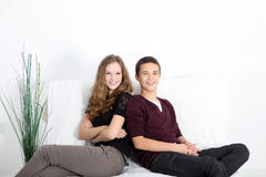 Teenaged couple relaxing at home. Young attractive smiling teenaged couple in trendy clothes relaxing at home reclining on a white sofa with copyspace Royalty Free Stock Photography