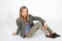 Teenaged girl. Sitting on white background Royalty Free Stock Photo