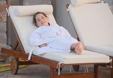 Teenaged girl in a bathrobe by the pool. Teenager resting after a swim in the oceanside pool on the Greek island of Crete Royalty Free Stock Photo