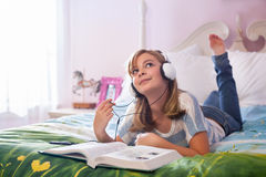 Teenaged girl on bed with headphones. Royalty Free Stock Photo