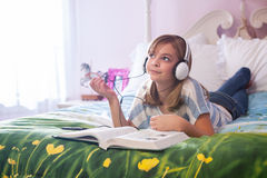 Teenaged girl on bed with headphones. Royalty Free Stock Photography