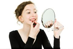 Teenaged girl in black dress making make up in mirror - lipstick royalty free stock photo