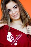 Teenaged Girl-Dreamstime Shirt. Attractive girl (minor) wearing a red dreamstime shirt, pulling collar down to expose skin stock photo