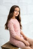 Teenaged girl in lace dress against brick wall. Beautiful teenaged girl in pink lace dress sitting on wooden chair against white wall Royalty Free Stock Photography