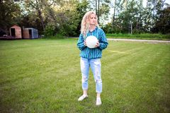 Teenaged girl outdoors with a volleyball. A teenaged girl in a sweater and jeans with long blonde curly hair fooling around with a volleyball in the backyard Stock Photo