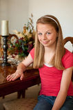 Teenaged girl sitting at wood dining table. Teenaged girl sitting with left side showing at wood finished dining room table at grandparents house with table Stock Image