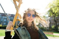Teenaged Girl with sun glasses swinging royalty free stock photos