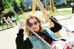 Teenaged Girl with sun glasses swinging royalty free stock photo