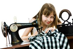Teenaged girl tailoress use manual sawing machine to sew her dress royalty free stock photography