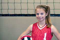 Teenaged girl volleyball player. In front of net with red shirt displaying confidence and a readiness to compete Royalty Free Stock Photography