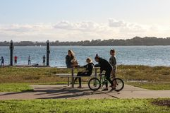Teenaged girls at a picnic table out by the water on a late Saturday afternoon in the Redlands  Queensland Australia May 23 2015. Teenaged girls at a picnic Royalty Free Stock Photos