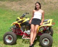 Teenaged Mädchen, das auf gelbem ATV sich lehnt Stockfotografie