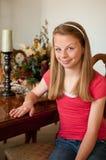 Teenaged Mädchen, das am hölzernen Speisetische sitzt Stockbild