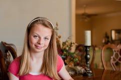 Teenaged Mädchen, das am hölzernen Speisetische sitzt Stockfotografie