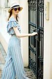 Teenaged Mädchen im Overallkleid öffnet geschmiedete Tore lizenzfreie abbildung