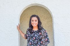 Girl Standing in Arched Doorway. A teenaged woman standing in an arched doorway with a white wall.  She is wearing a black floral blouse Stock Images