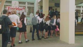 Teenagedkinderen in eenvormig met rugzakken en zakken dichtbij school eerst van september stock videobeelden