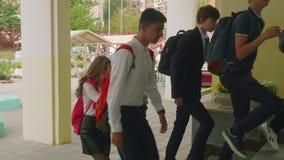 Teenagedkinderen in eenvormig met rugzakken en zakken dichtbij school eerst van september stock footage
