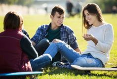 Teenagees chatting outdoor. Group of positive teenage friends chatting and having fun outdoor. Focus on girl royalty free stock images