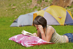 Teenager. Laying on grass reading a book Stock Photos