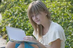 Teenager. Looks through notes in the park Stock Photography